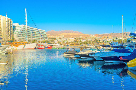 eilat: EILAT, ISRAEL - FEBRUARY 23, 2016: The bright colors of the morning city are reflected in waters of marina, full of yachts and boats, on February 23 in Eilat.