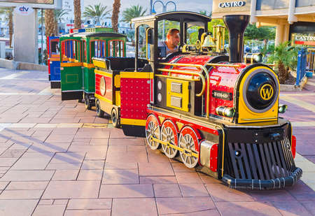 eilat: EILAT, ISRAEL - FEBRUARY 23, 2016: The colorful tourist train offers the pleasure rides along the promenade, on February 23 in Eilat.