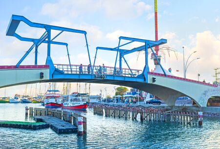 eilat: EILAT, ISRAEL - FEBRUARY 23, 2016: The modern drawbridge over the entrance to the marina with the yachts and pleasure  boats on the background, on February 23 in Eilat.