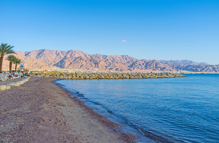 The evening empty beach with the stone pier and mountains of Jordan on the background, Eilat, Israel.