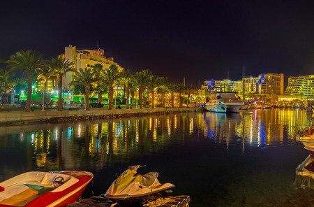 The scenic night view of marina with the bright lights, reflected in water, Eilat, Israel.