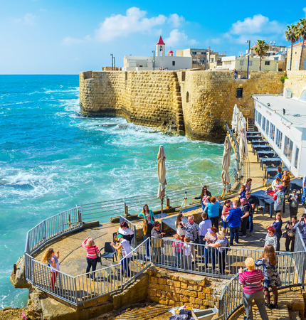 ACRE, ISRAEL - FEBRUARY 20, 2016: The tourists in the coastal viewpoint enjoy the Akko sea walls, preserved since the Middle Ages, on February 20 in Acre.