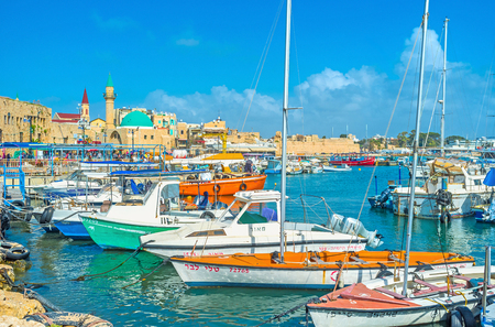acre: ACRE, ISRAEL - FEBRUARY 20, 2016: The yachts in the medieval port of Akko, named HaDayagim, with the green domed Sinan Basha Sea Mosque, on February 20 in Acre.