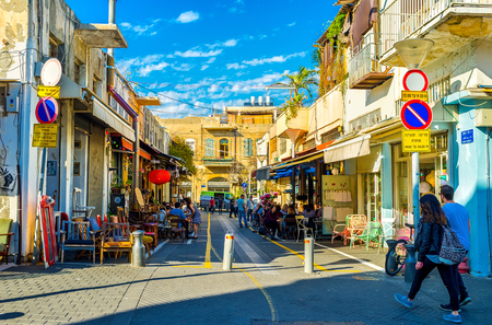 TEL AVIV, ISRAEL - FEBRUARY 25, 2016: The shady street of old Jaffa hides the cozy outdoor cafes and shops of retro furniture, so popular in the local flea market, on February 25 in  Tel Aviv.