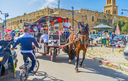 acre: ACRE, ISRAEL - FEBRUARY 20, 2016: The tourist carriage tries to ride inthe narrow port promenade of old Akko, on February 20 in Acre.