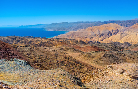 The dry rocky Eilat mountains with bright blue Aqaba Gulf on the background.