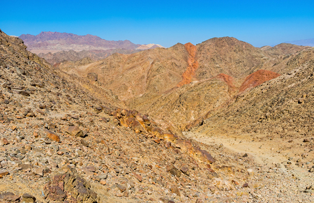 The narrow path among the steep rocky slopes leads to Zefahot Mount, Eilat, Israel.
