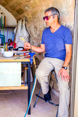 glassblower: CAESARIA, ISRAEL - MAY 19, 2016: The glassblower in his workshop next to the store, makes the souvenirs for tourists, on May 19 in Caesaria.