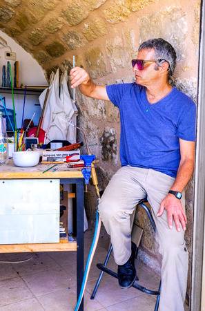 glassblower: CAESARIA, ISRAEL - MAY 19, 2016: The glassblower in his workshop makes the souvenirs for tourists, on May 19 in Caesaria.