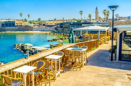 ancient israel: The outdoor restaurant in harbor of Caesaria overlooks the buildings, surrounding the port, bright blue water and tiny beach, Israel.