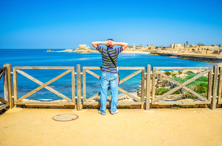 ful: The young tourist watches the coast of Caesaria ful of the ancient Roman ruins and picturesque places, Israel.