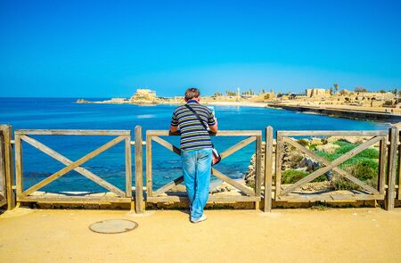 ancient buildings: The young tourist overlooks the coast of Caesarea with its ancient landmarks, Israel.