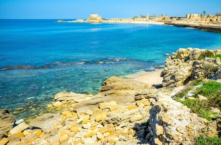 neighboring: The sharp rocks in Caesarea are neighboring with the cozy sand beaches, for those, who came to enjoy the National Park, Israel.