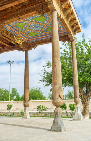 baha: The wooden terrace of Khakim Kushbegi Mosque, decorated with the carved wooden pillars and paintings on the roof, Bukhara, Uzbekistan.