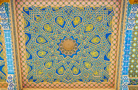 baha: BUKHARA, UZBEKISTAN - APRIL 29, 2015: The carved wooden screen on ceiling of Sheikh Naqshband Mausoleum decorated with painted stellar, geometric and floral patterns, on April 29 in Bukhara. Editorial
