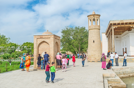 neighboring: BUKHARA, UZBEKISTAN - APRIL 29, 2015: The minaret of Khakim Kushbegi Mosque is neighboring with the modern ablution fountain, on April 29 in Bukhara.