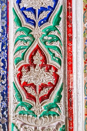 fretwork: BUKHARA, UZBEKISTAN - APRIL 29, 2015: The close-up of the tracery fretwork on ganch, painted in different colors in interior of Sitorai Mokhi-Khosa Palace, on April 29 in Bukhara.