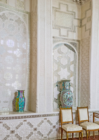 receptions: BUKHARA, UZBEKISTAN - APRIL 29, 2015: Thewall of the Hall for state receptions of Sitorai Mokhi-Khosa Palace, covered with lace of fretwork on ganch, on April 29 in Bukhara.