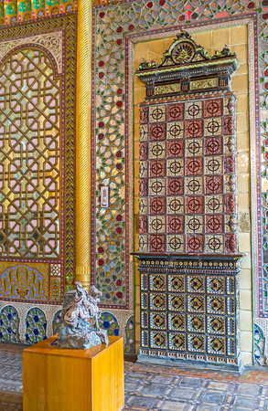 tiled stove: BUKHARA, UZBEKISTAN - APRIL 29, 2015: The tiled stove is built in wall of the dining room in Sitorai Mokhi-Khosa Palace, on April 29 in Bukhara.