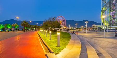 streetlights: Panorama of the seaside promenade with the red bike lane, raw of the streetlights and the ferris wheel on the background, Batumi, Georgia.