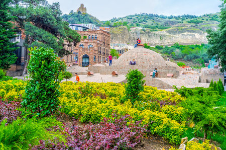 hamam: TBILISI, GEORGIA - MAY 28, 2016: The  sulfur baths and garden of Abanotubani is the favorite place of children, enjoying the games among the brick domes, on May 28 in Tbilisi.