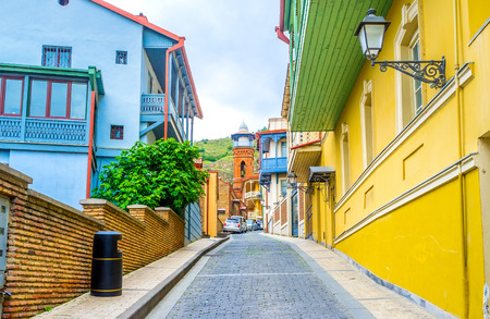 The street with the colorful cottages in Abanotubani district ends with the brick minaret of Jumah Mosque, Tbilisi, Georgia. Stockfoto