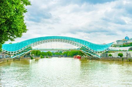 The modern Peace Bridge over Kura River in Tbilisi center, made of metal and glass, Georgia.