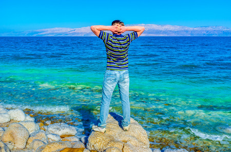 gedi: The man on the shore of the Dead Sea enjoy being in Earths lowest elevation on land, Ein Gedi, Israel.