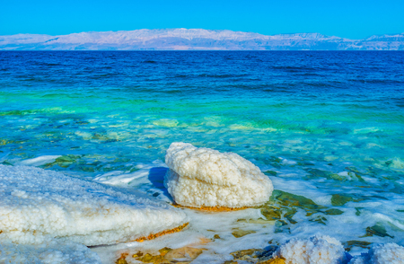 gedi: The thick layer of salt covers the stones, instantly drying in the sun on the Dead Sea shore, Ein Gedi, Israel. Stock Photo