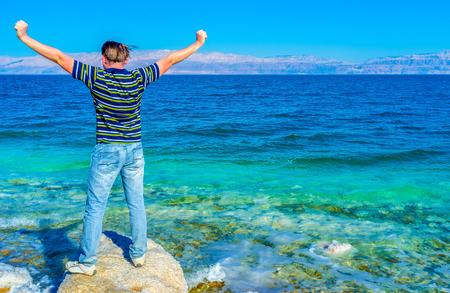 gedi: The happy man enjoy the beauty of the Dead Sea, Ein Gedi, Israel. Stock Photo