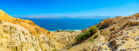judean desert: The rocky yellow slopes of Ein Gedi Nature Reserve with the bright blue waters of Dead Sea and mountains of Jordan on background, Judean desert, Israel.