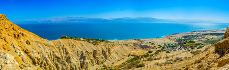 kibbutz: The mountains of Judean desert overlook the Dead Sea and its coastline with green palms of the local kibbutz, Ein Gedi, Israel. Stock Photo