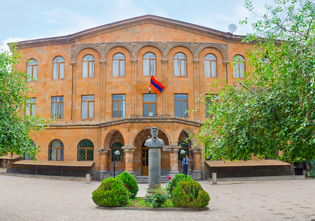 YEREVAN, ARMENIA - MAY 29, 2016: The facade of Anton Chekhov Basic School with the monument to this famous Russian writer in front of it, on May 29 in Yerevan.