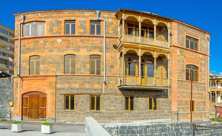 The fine example of traditional Armenian architecture, house built of colorful stone bricks with the carved wooden balcony, Yerevan.