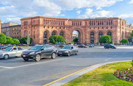 building monumental: YEREVAN, ARMENIA - MAY 29, 2016: The monumental red stone building with the arched pass in the middle, is the part of Republic Square architectural complex, on May 29 in Yerevan.