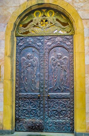 eligion: TBILISI, GEORGIA - MAY 28, 2016: The entrance to Anchiskhati Basilica of St Mary, decorated with icons and traceries, stamped on metal, on May 28 in Tbilisi.