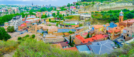 sunni: The old Abanotubani neighborhood with the brick domes of Sulphur Baths, minaret of Jumah Mosque, colorful roofs and rocky slope of the Fig Gorge, Tbilisi, Georgia.