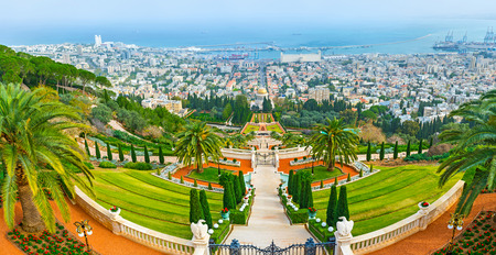 The perfectly landscaped terraced Bahai Gardens on the slope of Carmel Mount with the buildings of Haifa and Mediterranean coast in the distance, Israel.