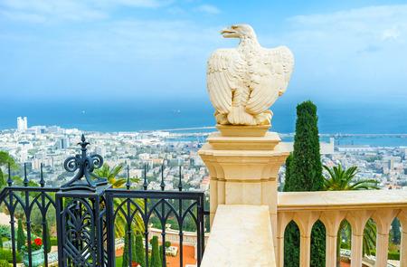 The white stone eagle guards the gate to Bahai Gardens and overlooks the cityscape and coast of Haifa, Israel.