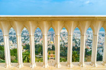 The view on Bahai Gardens and Shrine through the white stone handrail on the top of Carmel Mount, Haifa, Israel. Stock Photo
