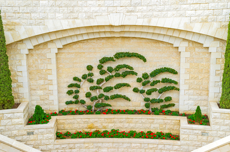 bahai: The decorative wall of Bahai Gardens with the flower beds and tiny trimmed  trees, Haifa, Israel. Stock Photo