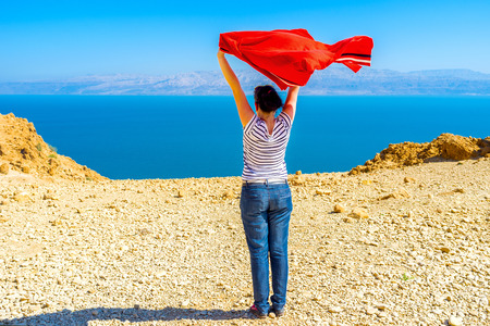 judean desert: The girl enjoy the fresh  air, watching the Dead Sea, standing on the mountain top in Judean Desert, Ein Gedi, Israel.