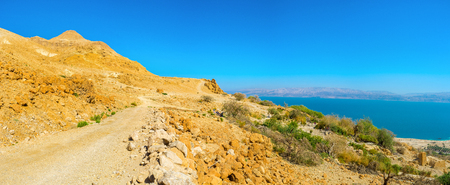 The road into the distance in the mountains of Judean Desert with the view on the Dead Sea, Ein Gedi, Israel.