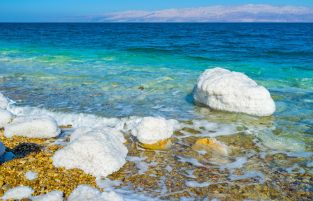 The calm shore of the Dead Sea with the white stones, covered with salt, Ein Gedi, Israel.