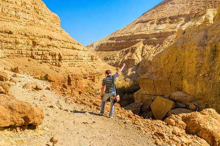 dea: The young tourist feals completely happy after the long climbing on the rocky slope of the gorge in Ein Gedi, Israel. Stock Photo