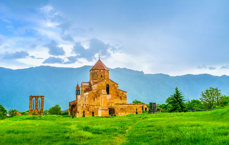 peculiarities: After the rain the  Odzun Basilica gets brighter shade because of peculiarities of local stone, Odzun, Alaverdi, Armenia. Stock Photo