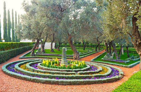 The round flower bed consists of many rows of colorful flowers with the Oriental park sculpture in the middle, Bahai Gardens, Haifa, Israel.