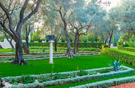 The small sculpture of the eagle, waving his wings, in shade of trees in Bahai Garden, Haifa, Israel. Stock Photo