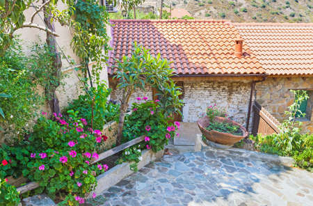 The village street with the stone floor and the scenic garden in front of the old house, Gourri, Cyprus. Reklamní fotografie