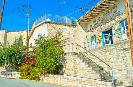 of pano: The stone house in the hilly street with the lush flower bushes, next to its wall, Kato Drys, Cyprus.
